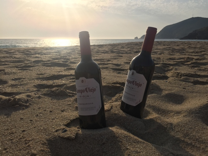 Wine bottles on the beach at sunset